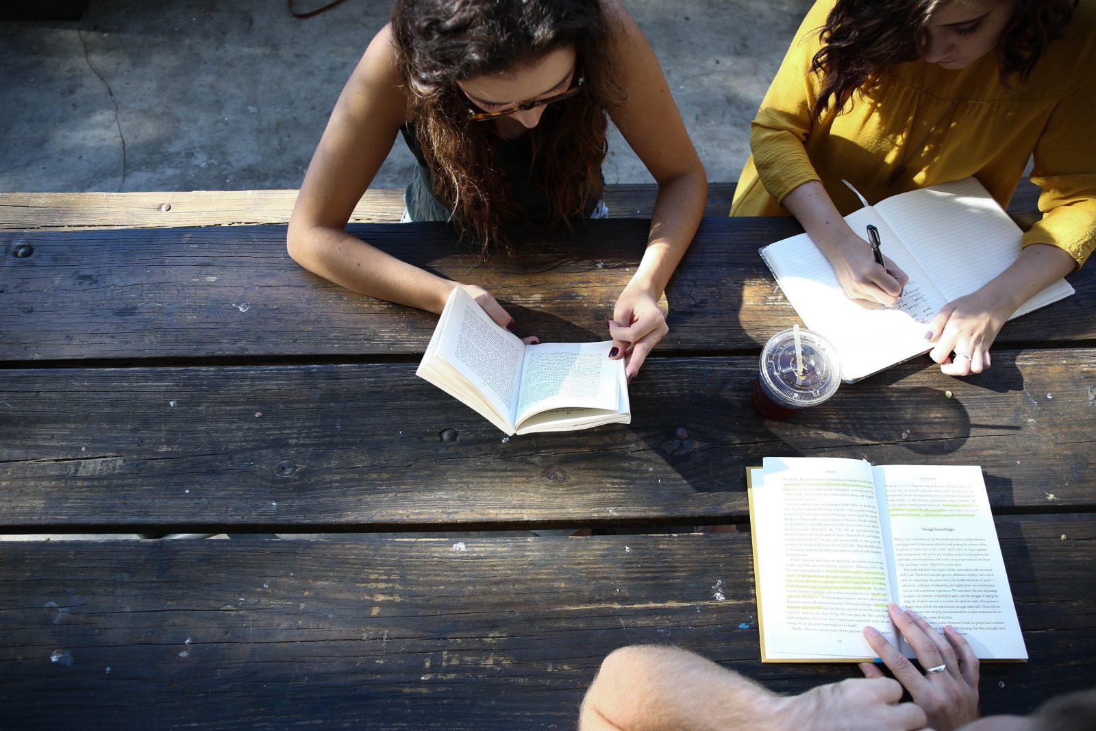 Ulkona puisen pöydän äärellä ihmisiä jotka lukevat kirjaa.
