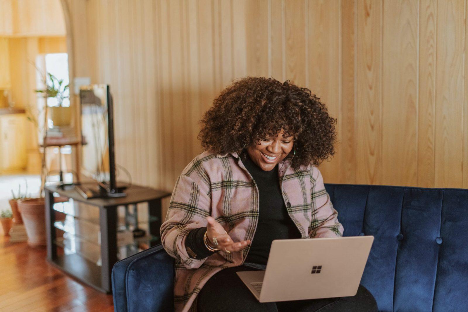 En kvinna leer och ser på datorn