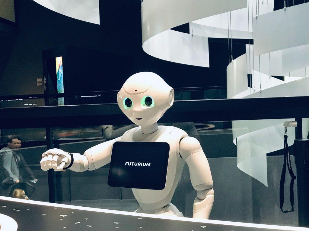 Valkoinen robotti ojentaa kättä ja katsoo kameraan.
