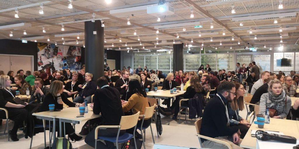 Människor sitter vid border i seminarrummet