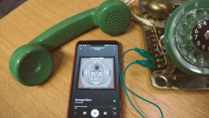 Älypuhelimessa auki Spotify ja puhelin on kiinnitettynä lankapuhelimeen