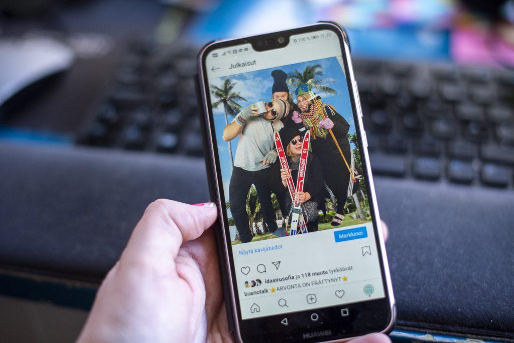 Puhelinta pidetään kädessä ja siinä auki Buenotalkin Instagram-postaus
