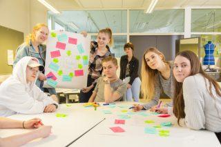 Ryhmä nuoria istuu pöydän ympärillä ja yksi pitelee fläppitaulun paperi, jossa on värikkäitä post-it lappuja