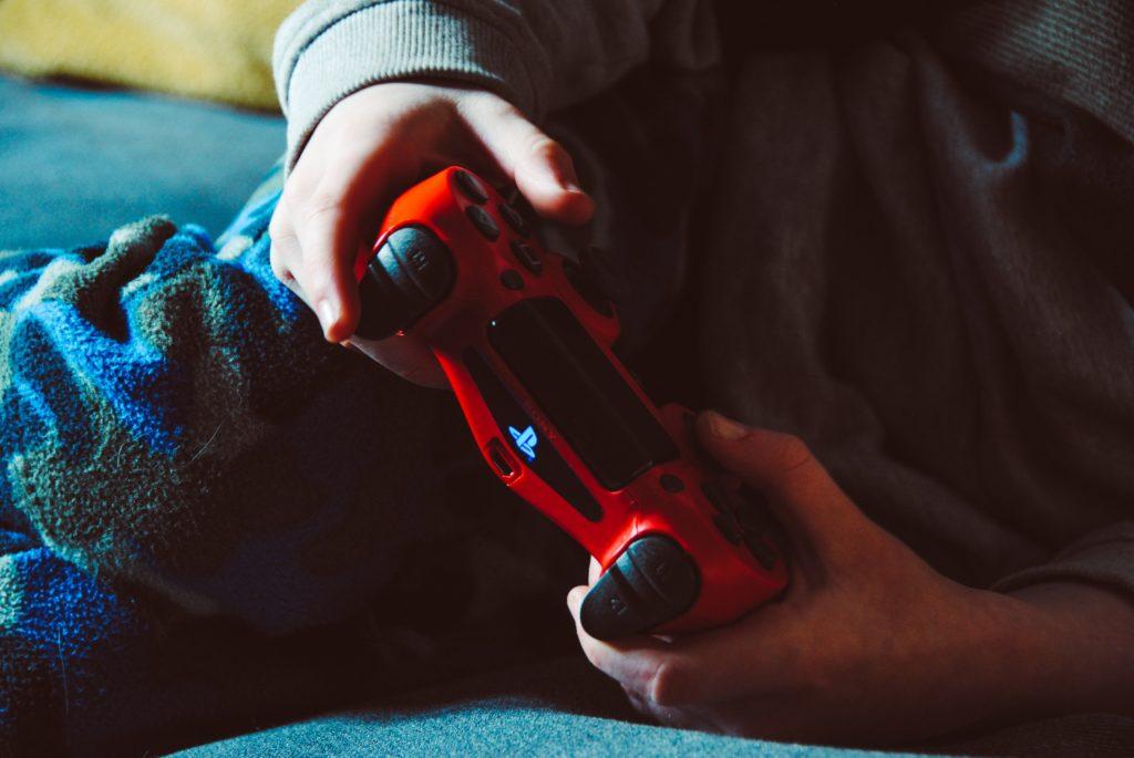 Henkilö pitää punaista Playsation ohjainta kädessään.