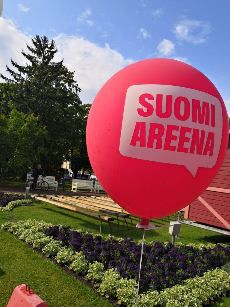 Pinkki ilmapallo, jossa lukee SUOMI AREENA, taustalla puistomaisema.