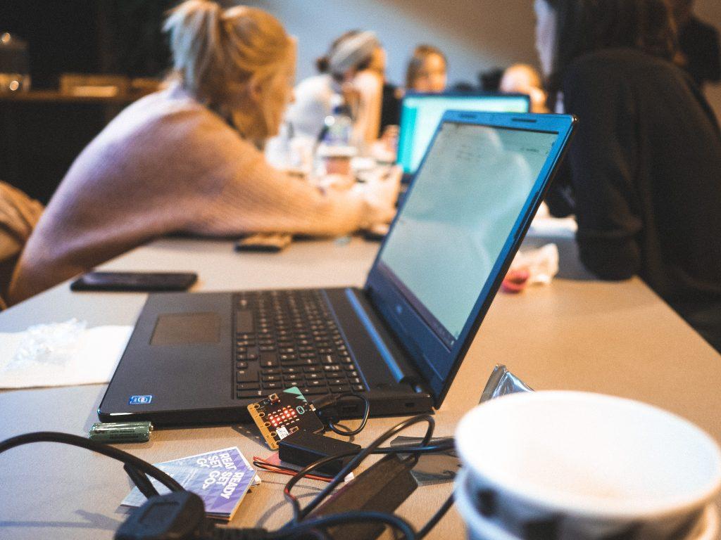 Etualalla tietokone auki ja taustalla vaaleahiuksinen nainen.