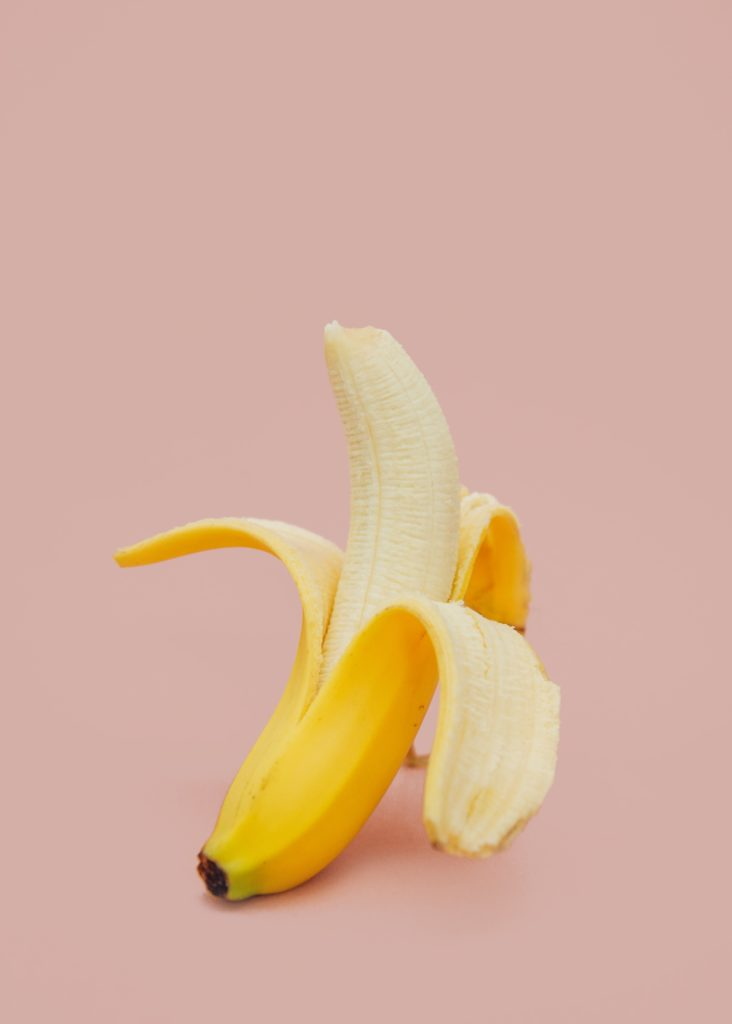 Puoliksi kuorittu banaani pinkillä taustalla.