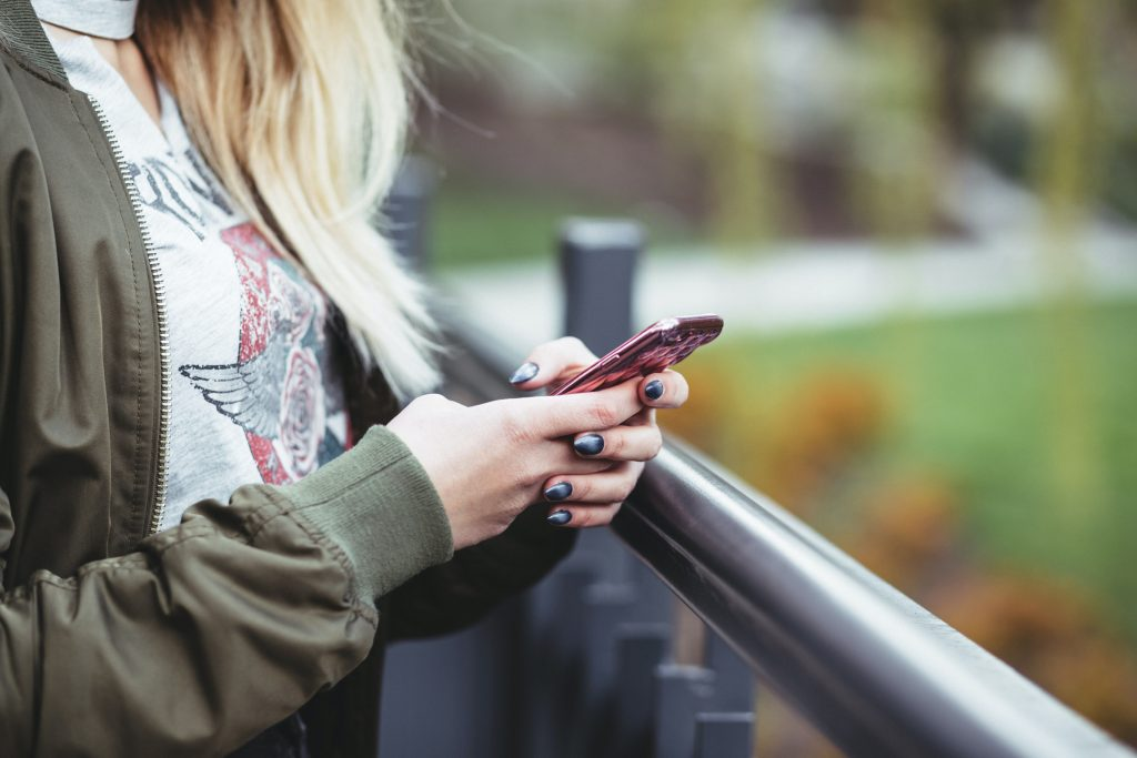 Ihminen pitää puhelinta kädessä vartalon edessä ulkomaisemissa.