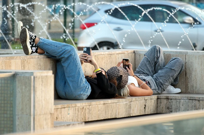 Kaksi nuorta makaa puistonpenkillä ristikkäin puhelimet kädessä.