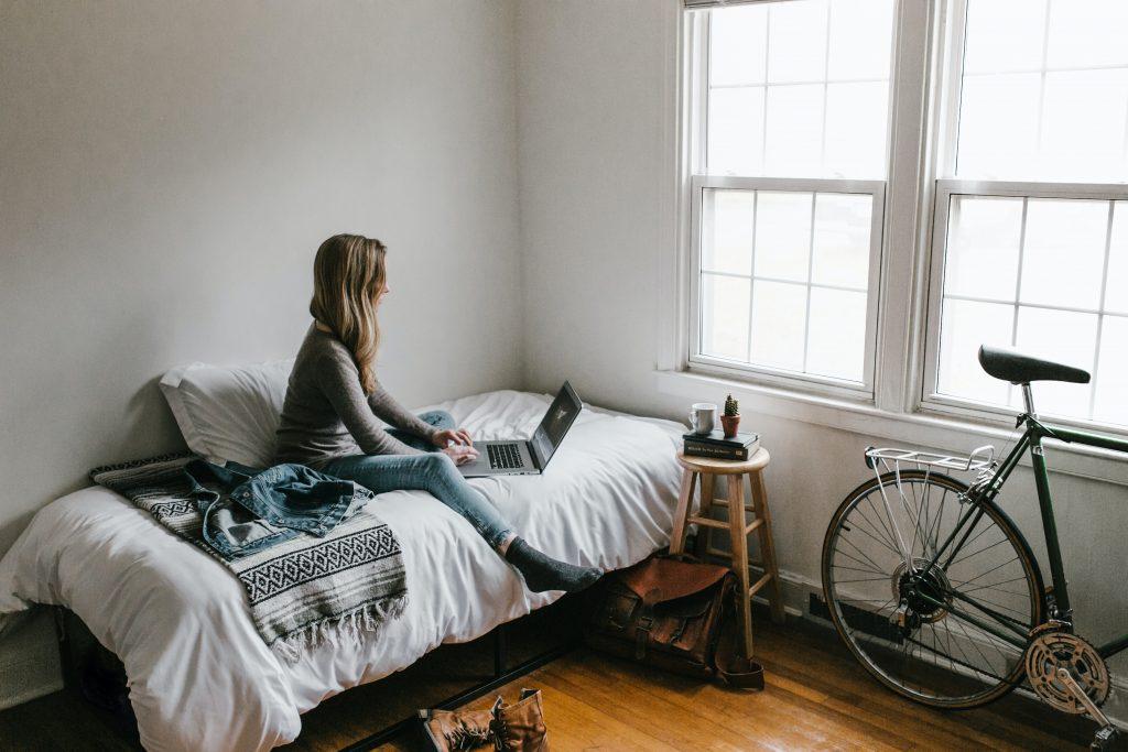 Nainen istuu sängyllä ja katsoo tietokonetta.