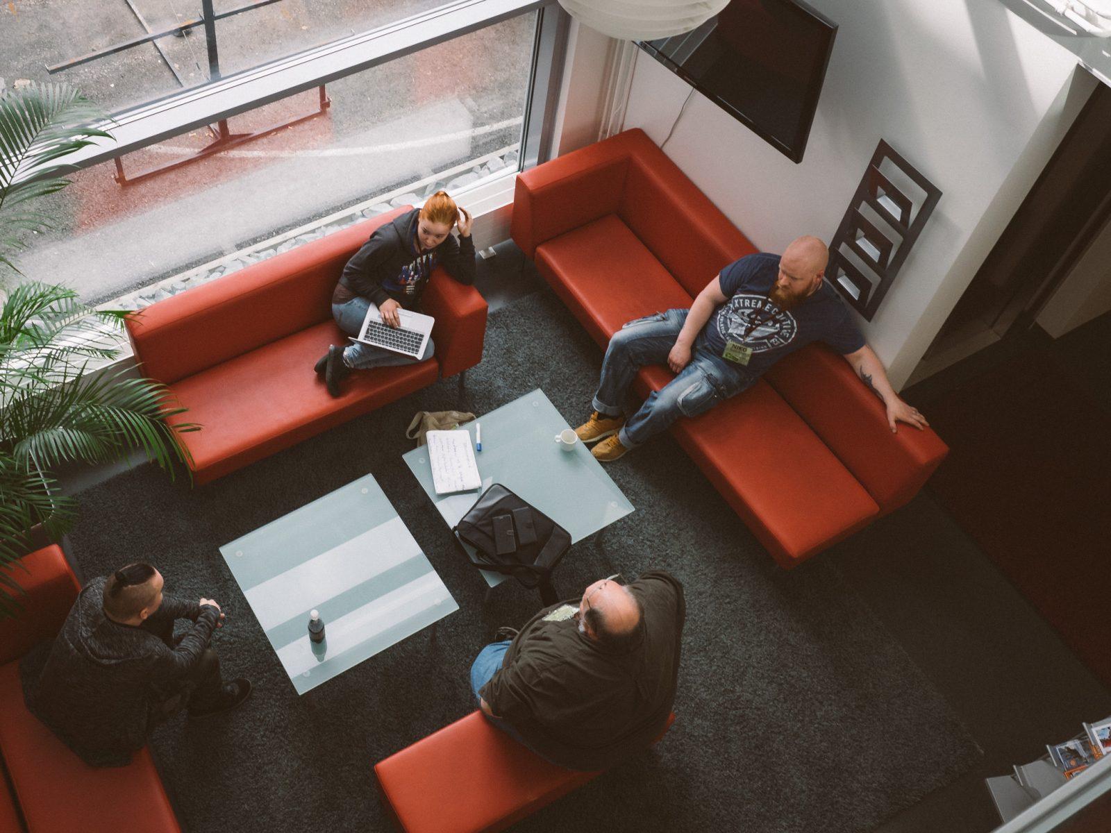 Neljä henkilöä istuu punaisilla sohvilla.