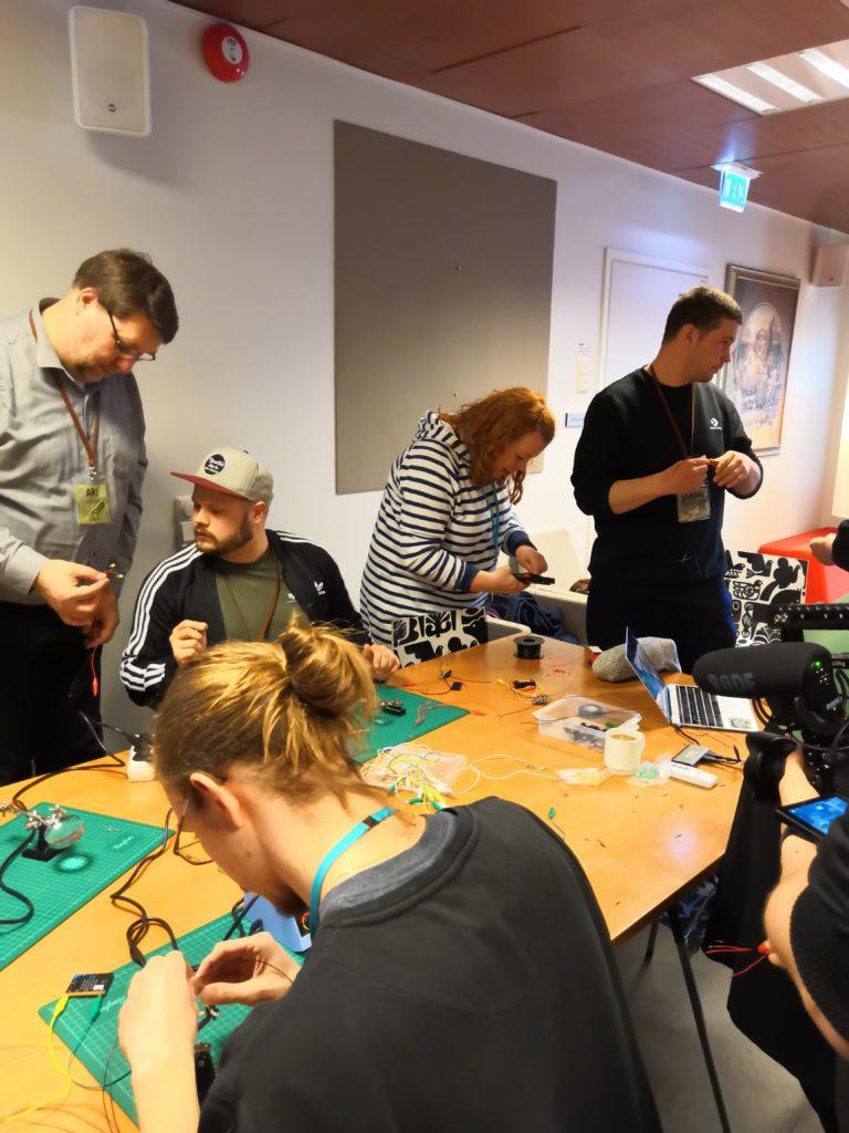 Ihmiset kokooontuneena pöydän äärelle Maker-toiminnan parissa.