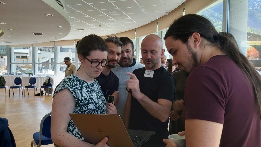 Henkilöt kokoontuneena katsomaan tietokoneen näyttöä.