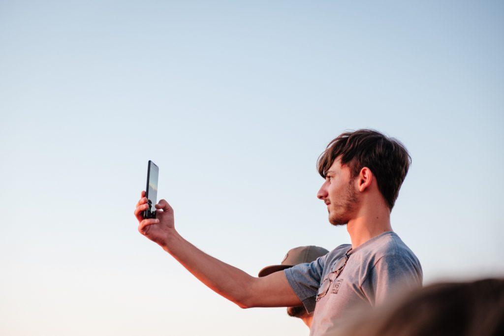Mies pitelee puhelinta kädessään, taustalla näkyy taivas.