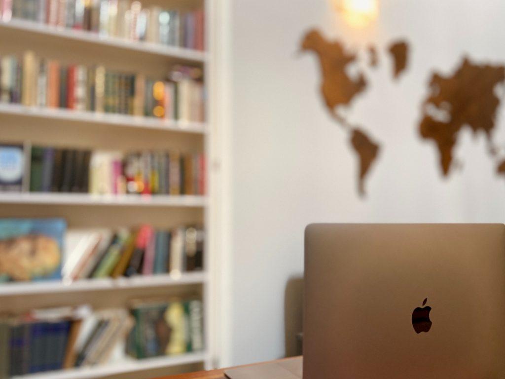 Läppärin kansi auki pöydällä ja takana kirjahylly sekä seinällä maailman kartta.