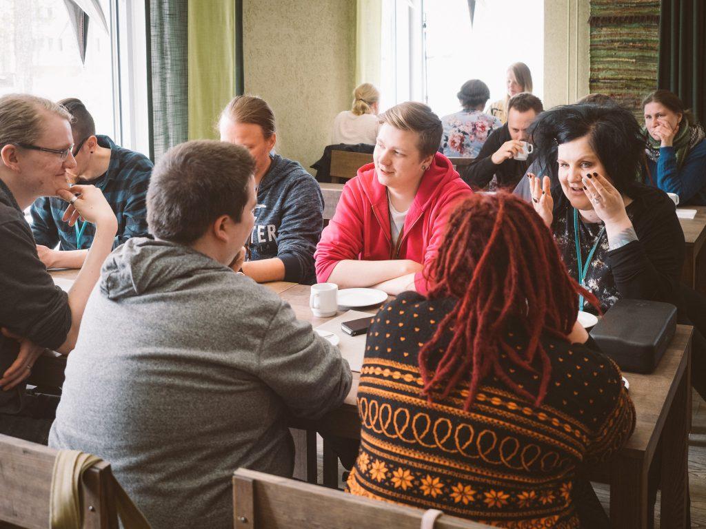 Ihmisiä istuu pöydän ympärillä juttelemassa.