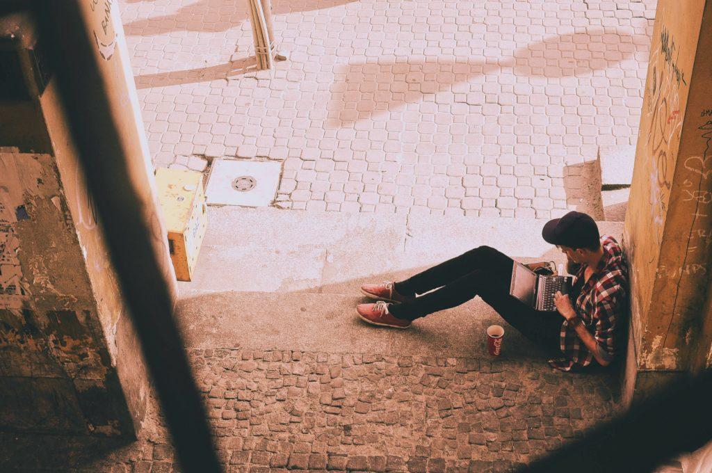Henkilö istuu maassa seinää vasten nojaten ja kirjoittaa tietokoneella.