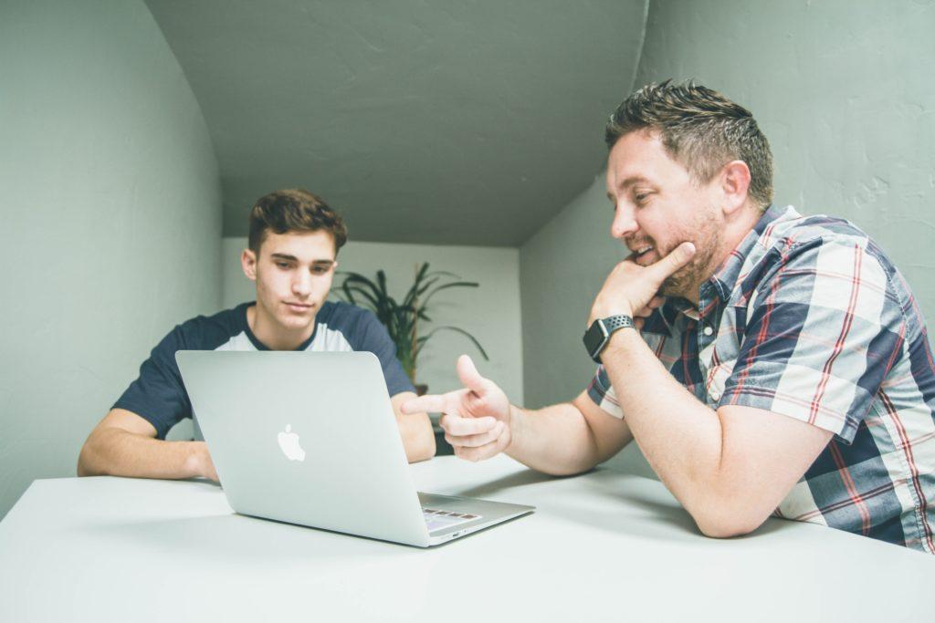 Kaksi miestä istuu pöydän äärellä ja katsoo saman tietokoneen näyttöä
