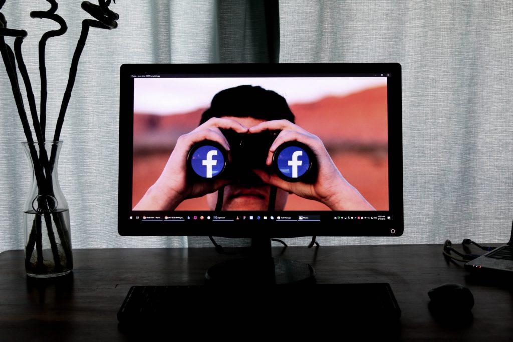 Kuva tietokoneesta, jonka näytöllä kuva henkilöstä joka katsoo kameeranpäin kiikareiden läpi. Kiikareiden linssien kohdalla on Facebook-logot.