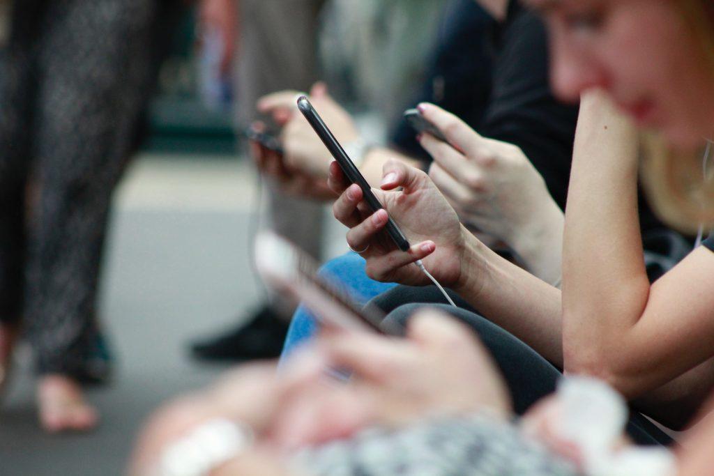 Vierekkäin istuvat ihmiset selaavat puhelimiaan