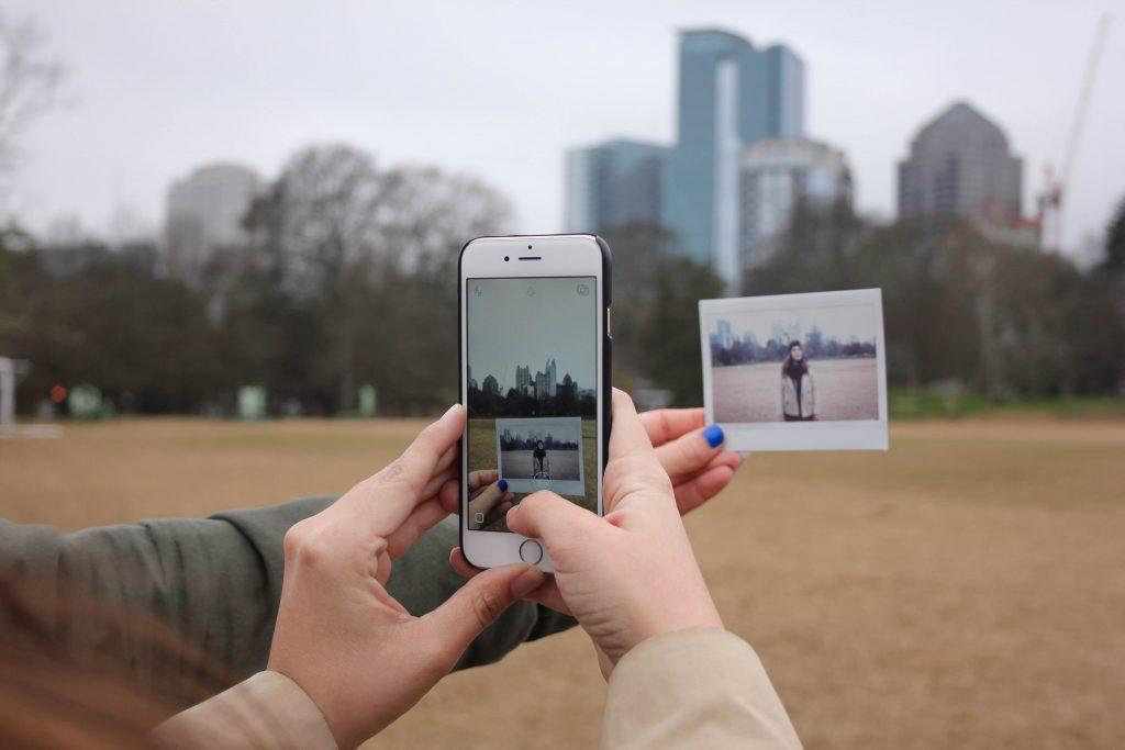 Ouhelimella otetaan kuvaa polaroid-kuvasta ulkona.