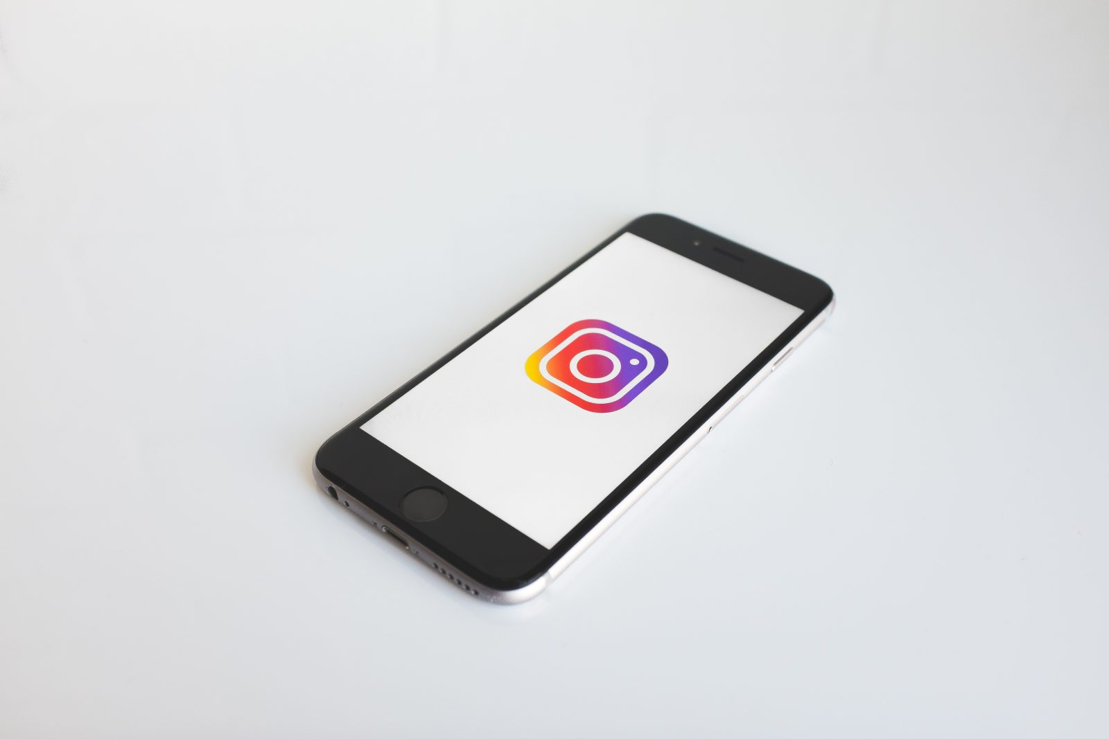 Valkoisella taustalla makaa puhelin, jossa on auki Instagramin logo.
