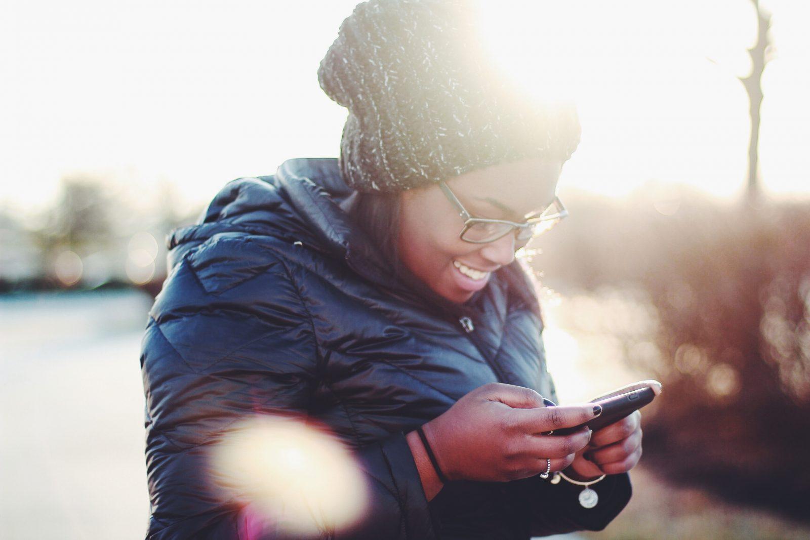 Nainen on takki päällä ulkona puhelin kädessä ja katsoo nauraen ruutua auringon paistaessa takana.