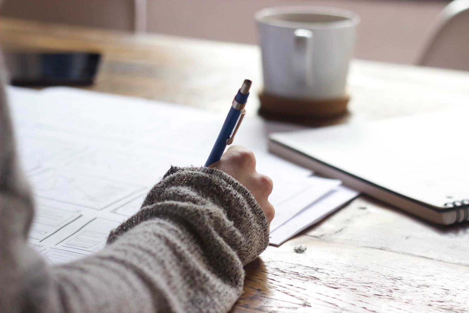 Käsi kirjoittaa pöydän äärellä vihkoon