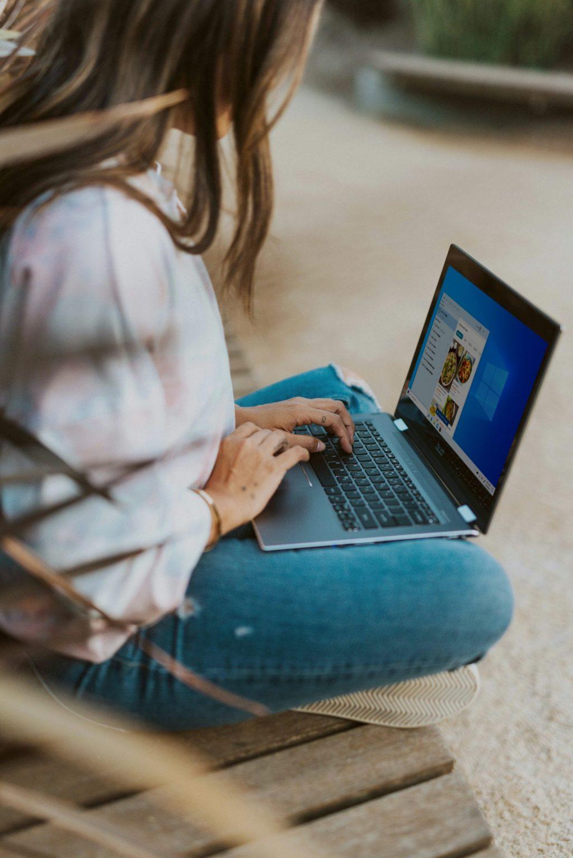 Nainen istuu ulkona tietokone sylissä