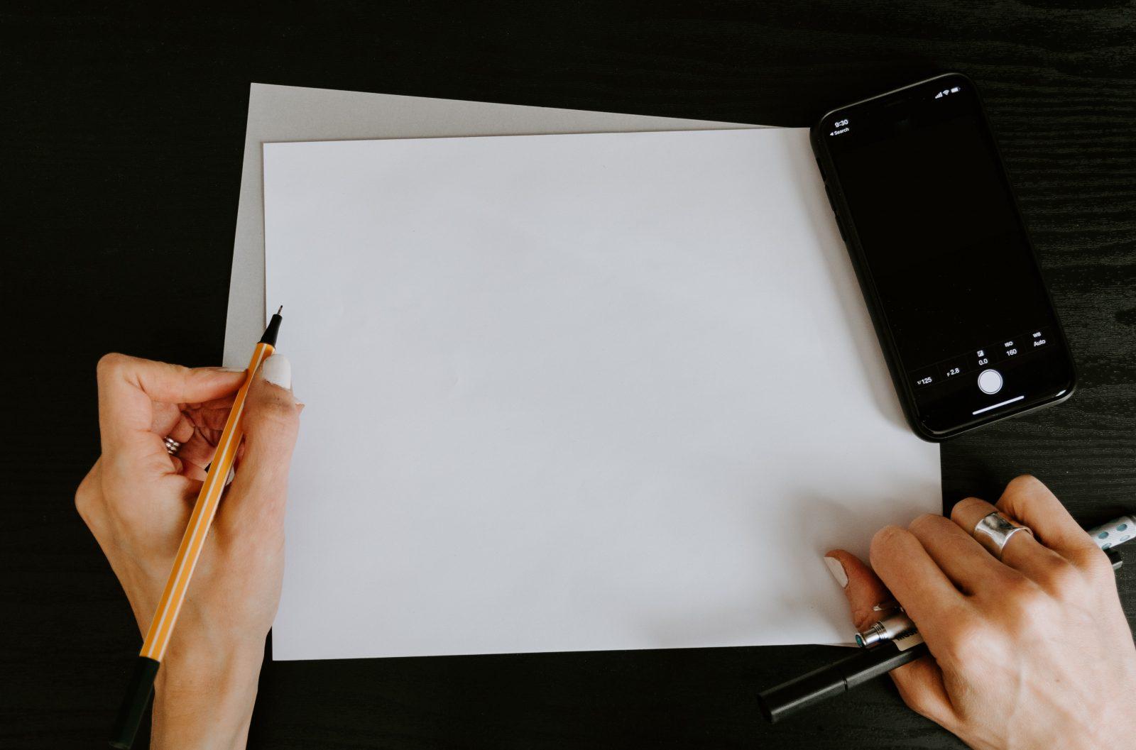 Käsissä on tyhjä valkoinen paperi ja kynä.