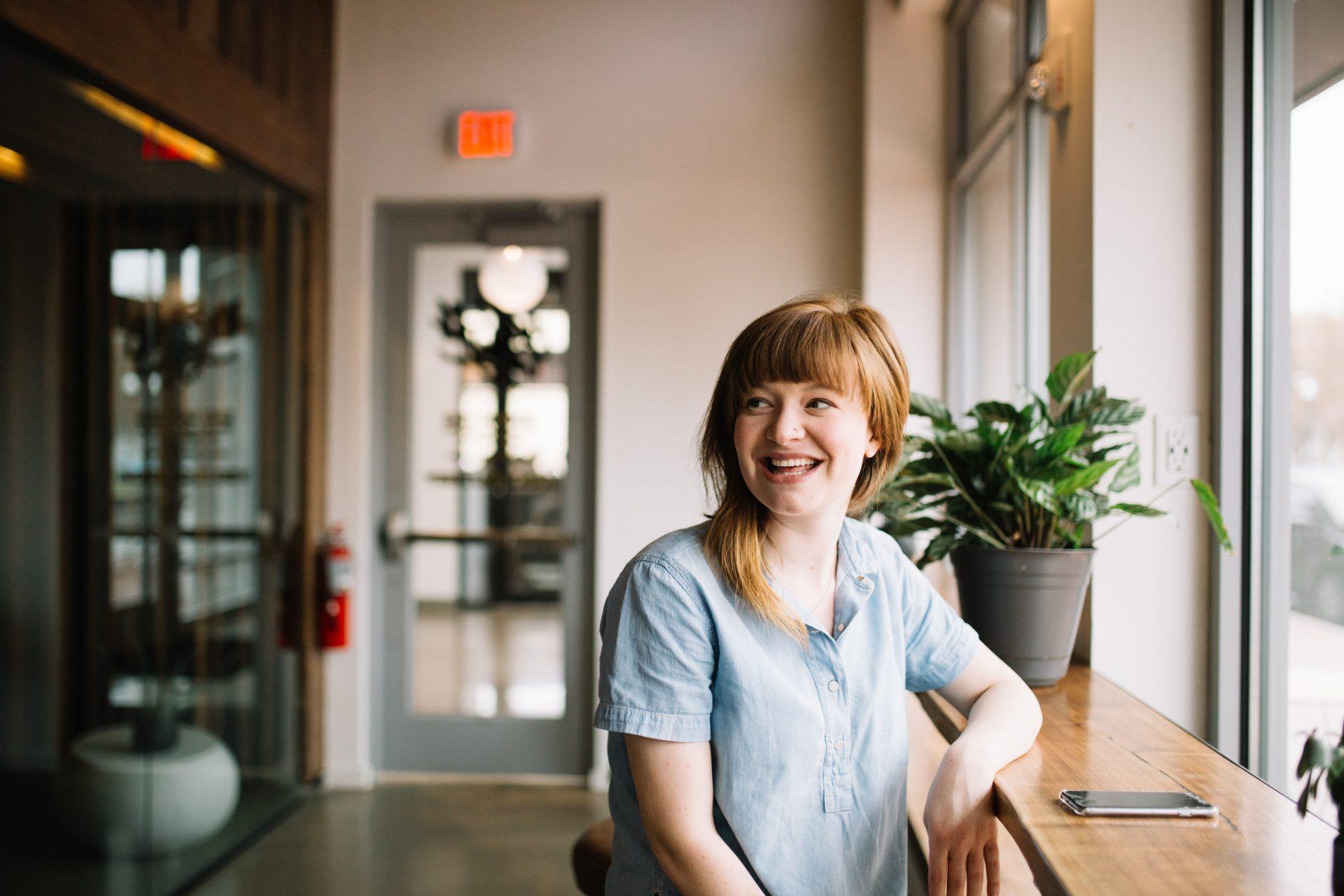 Nainen istuu kahvilassa ikkunan edessä olevassa baaripöydässä ja katsoo hymyillen sivulle.
