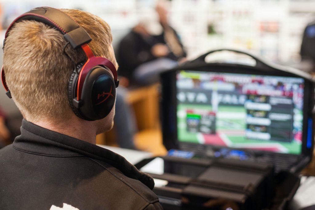 Henkilö pelaa kuulokkeet korvilla peliä.