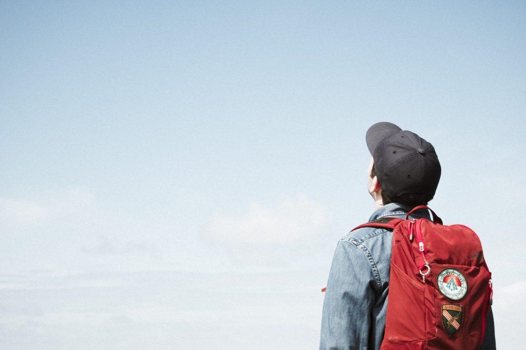 Henkilö seisoo taivasta vasten ja katsoo reppu selässä ylöspäin.