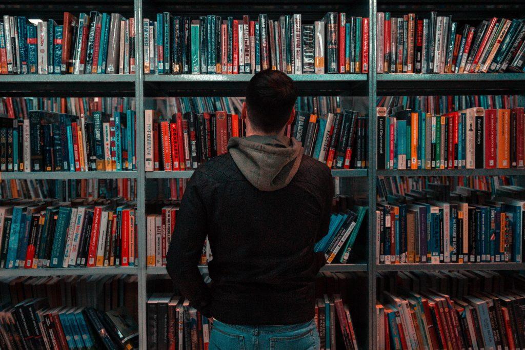 Mies seisoo kirjahyllyn edessä pimeähkössä huoneessa.