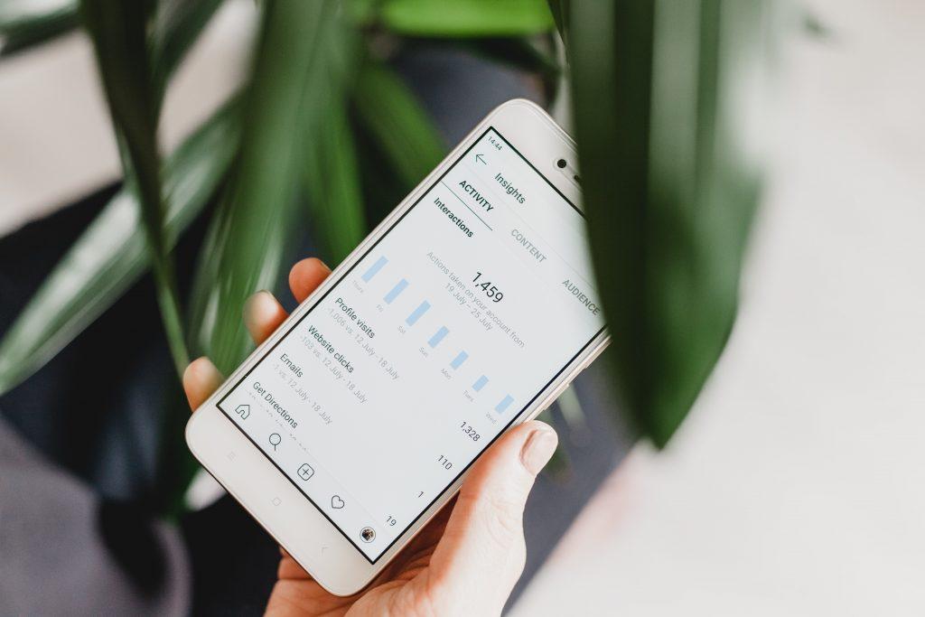 Puhelinta pidetään kädessä viherkasvin luona ja puhelimessa on auki Instagramin analytiikkaa.