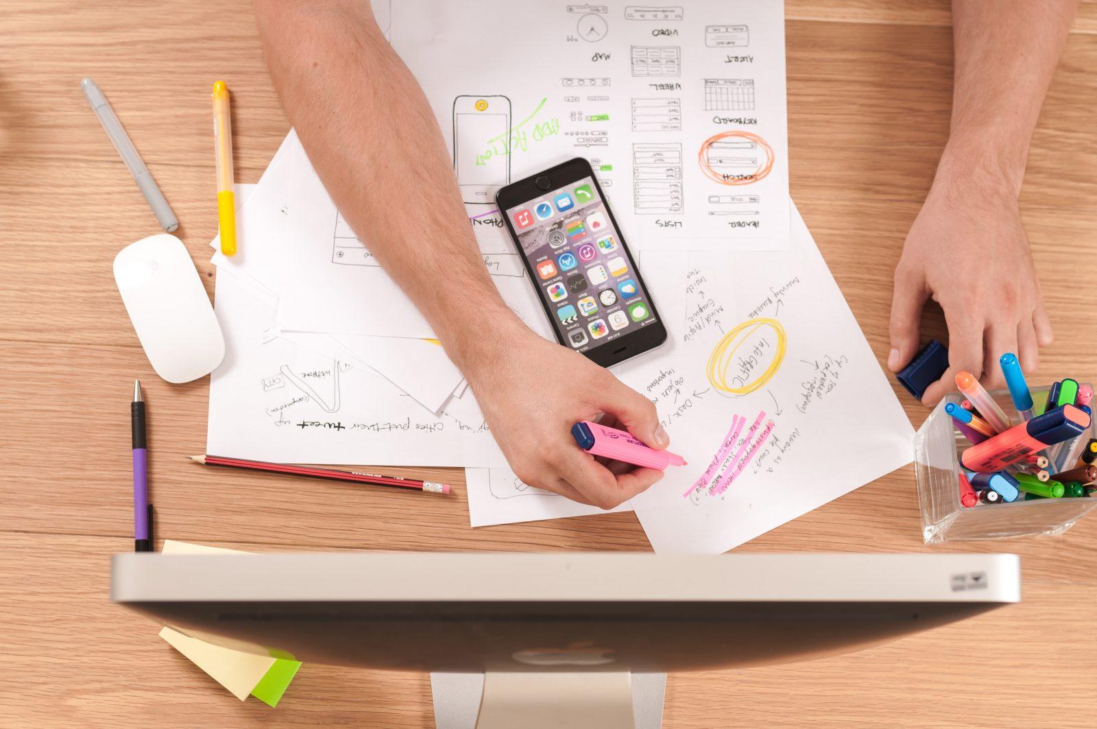 Mies suunnittelee sosiaalisen median käyttöä pöydän ääressä