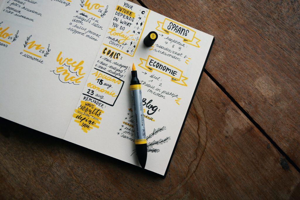paperin päällä on kynä ja kirjoitettu tekstiä sekä keltaisia viivoja.