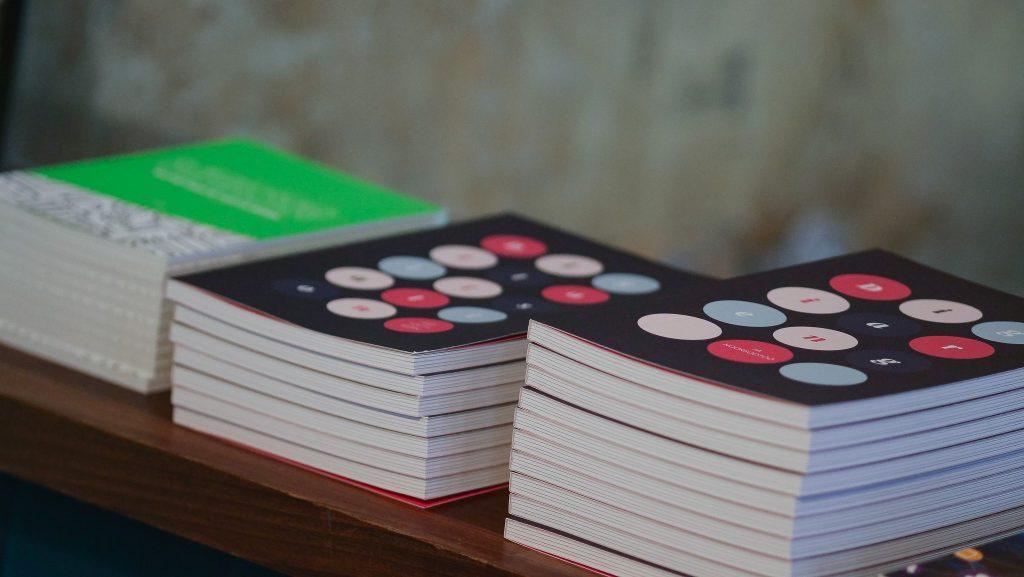 Verken julkaisuja pinottuna pöydälle