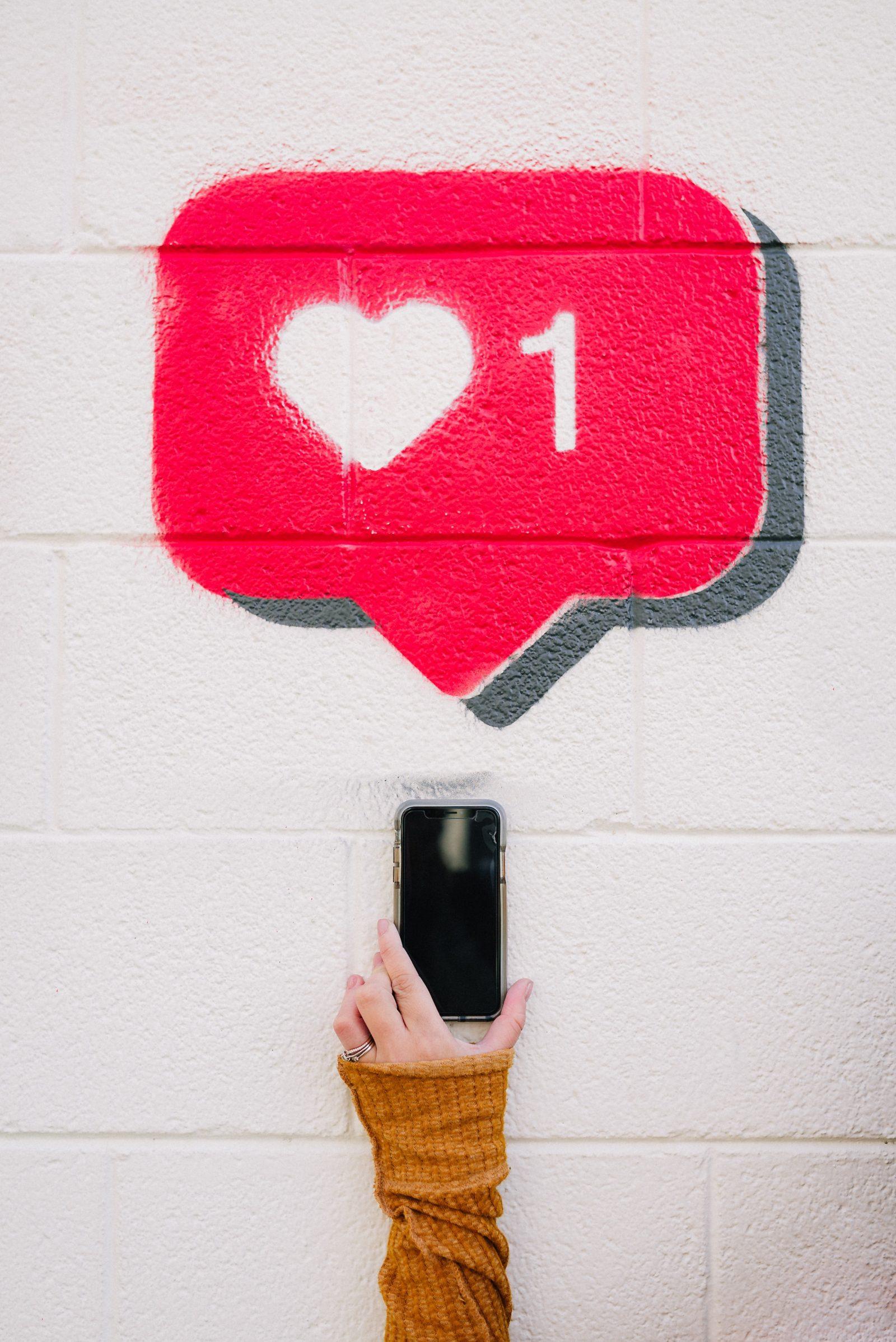 Puhelinta pidetään seinän edessä johon on maalattu somen tykkäyskuvake.