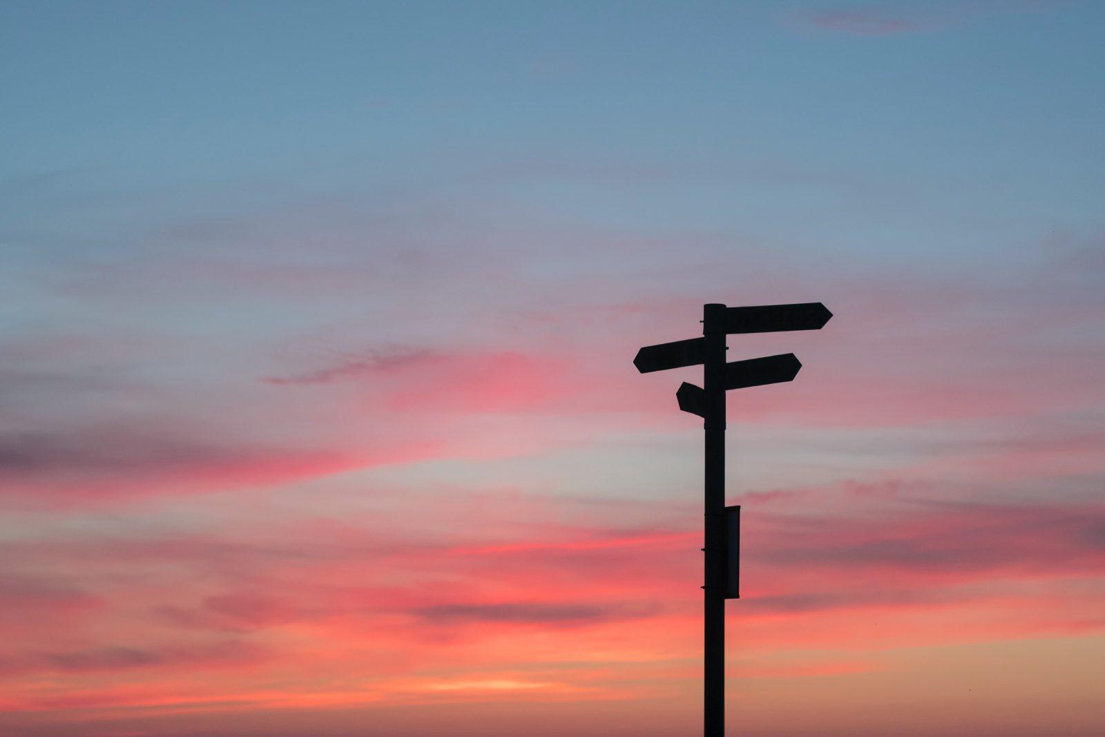 Auringonlaskussa tiekyltti, joka soittaa moneen eri suuntaan.