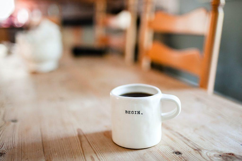Pyypöydällä kahvikuppi, jossa lukee begin.