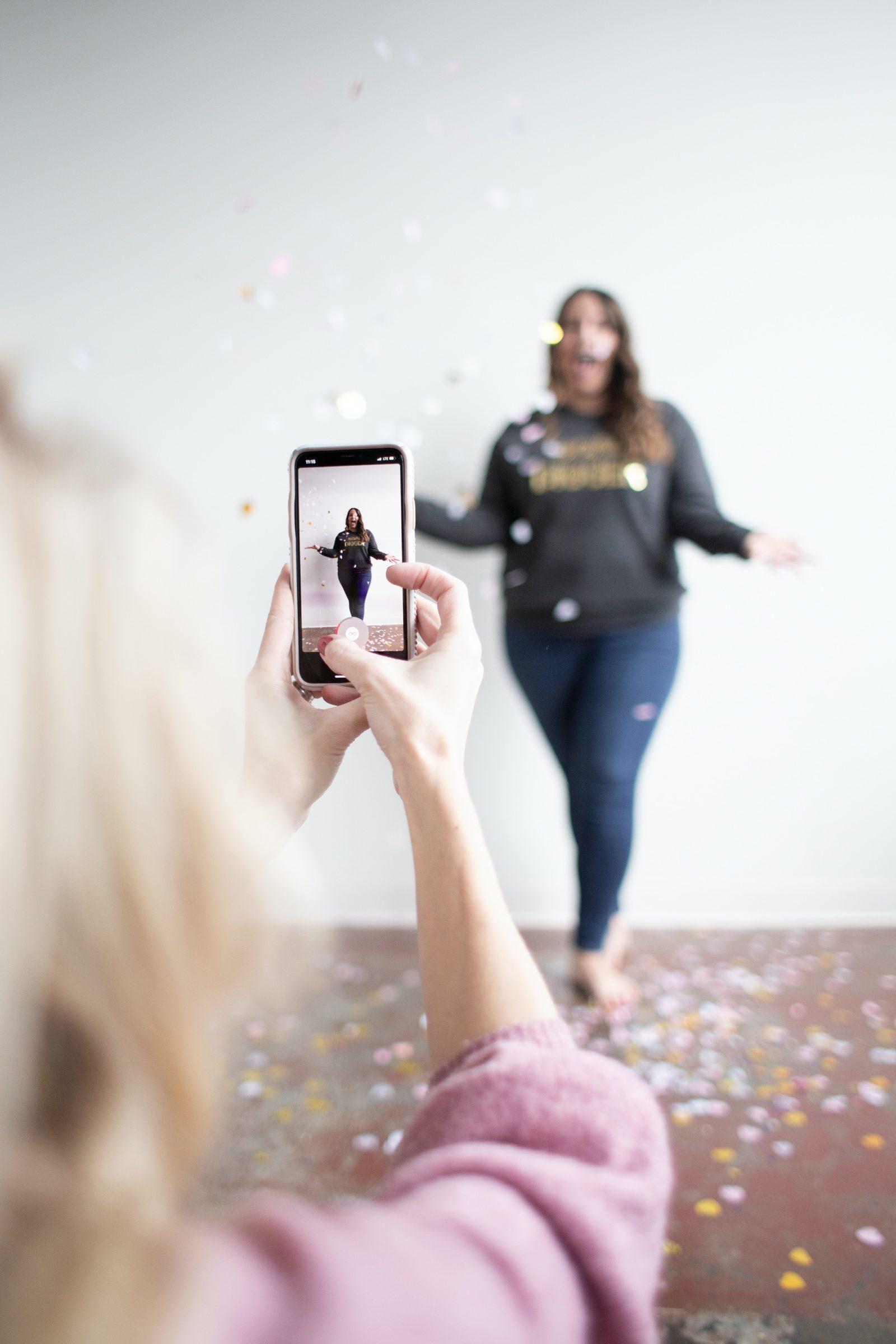 Nainen kuvaa toista naista puhelimella seisomassa seinän edessä ja heittämässä konfetteja ilmaan.