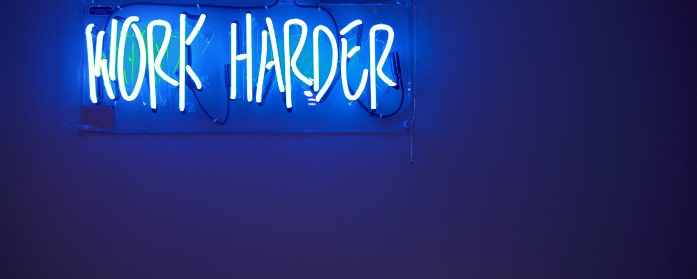 Work harder -valokyltti seinällä.