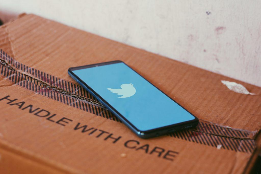 Pahvilaatikon päällä puhelin, jossa on auki Twitterin logo.