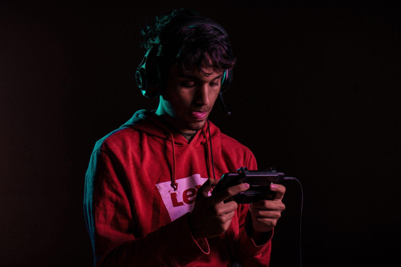 Tummassa kuvassa seisoo mies, jolla pelikonsoli ja kuulokkeet.