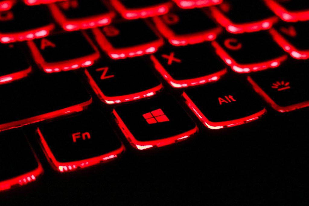 Tietokoneen musta näppäimistö, jossa on punaiset valot