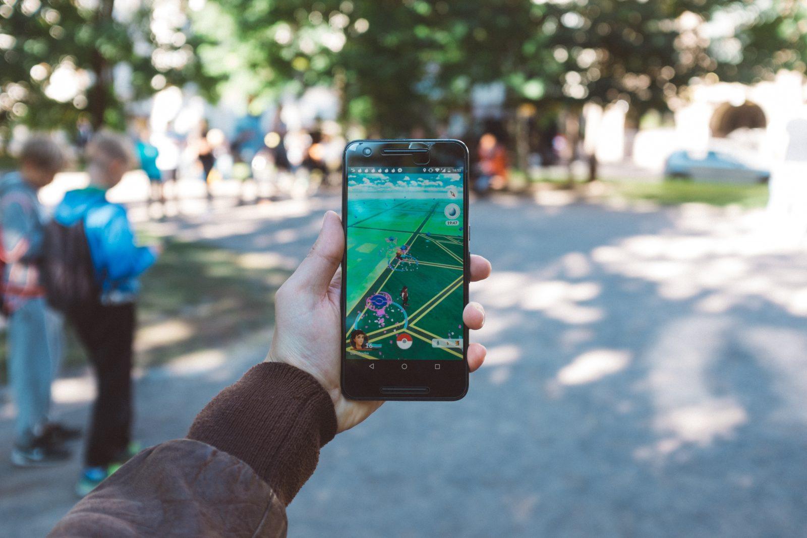 Kädessä pidetään pihalla puhelinta, jossa on auki Pokemon Go.