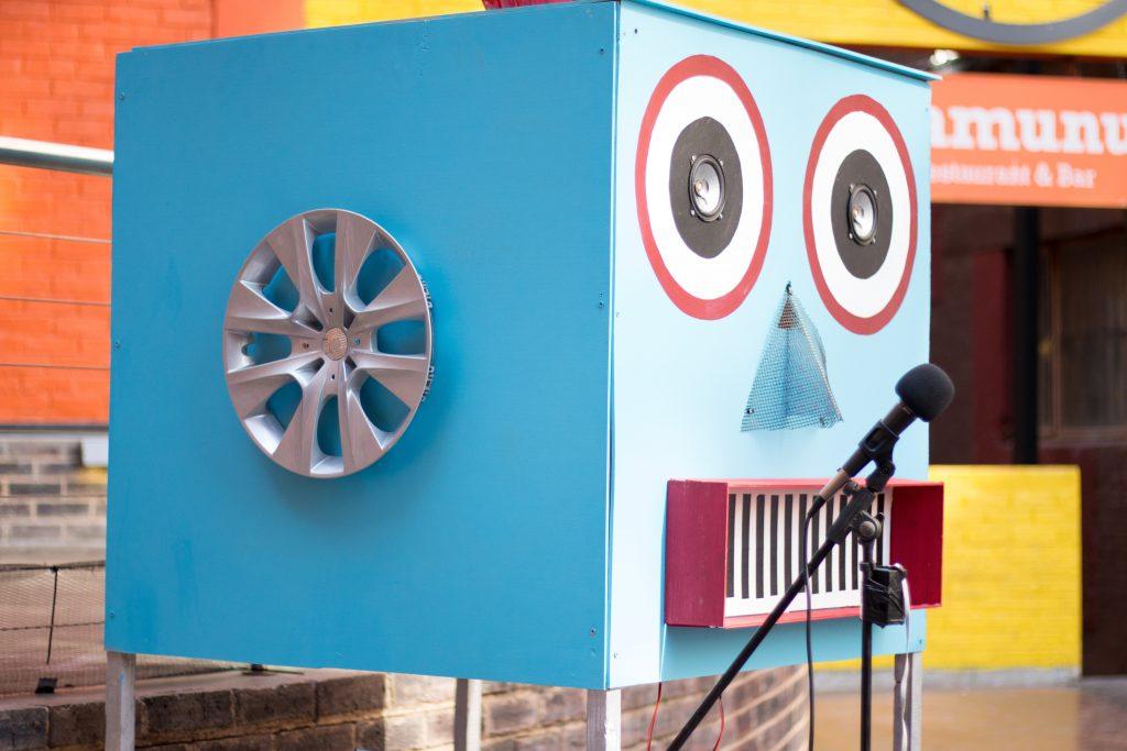 Itse rakennettu sininen pahvilaatikko robotti mikrofonin edessä.