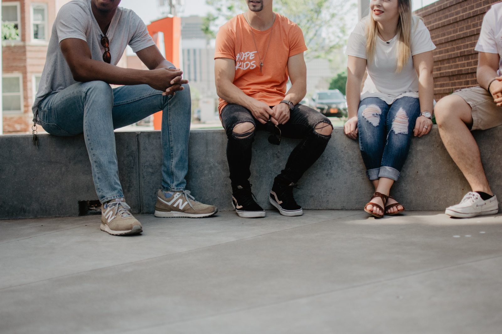 Ihmisiä istuu ulkona vierekkäin, kuvassa näkyy vain alavartalo.