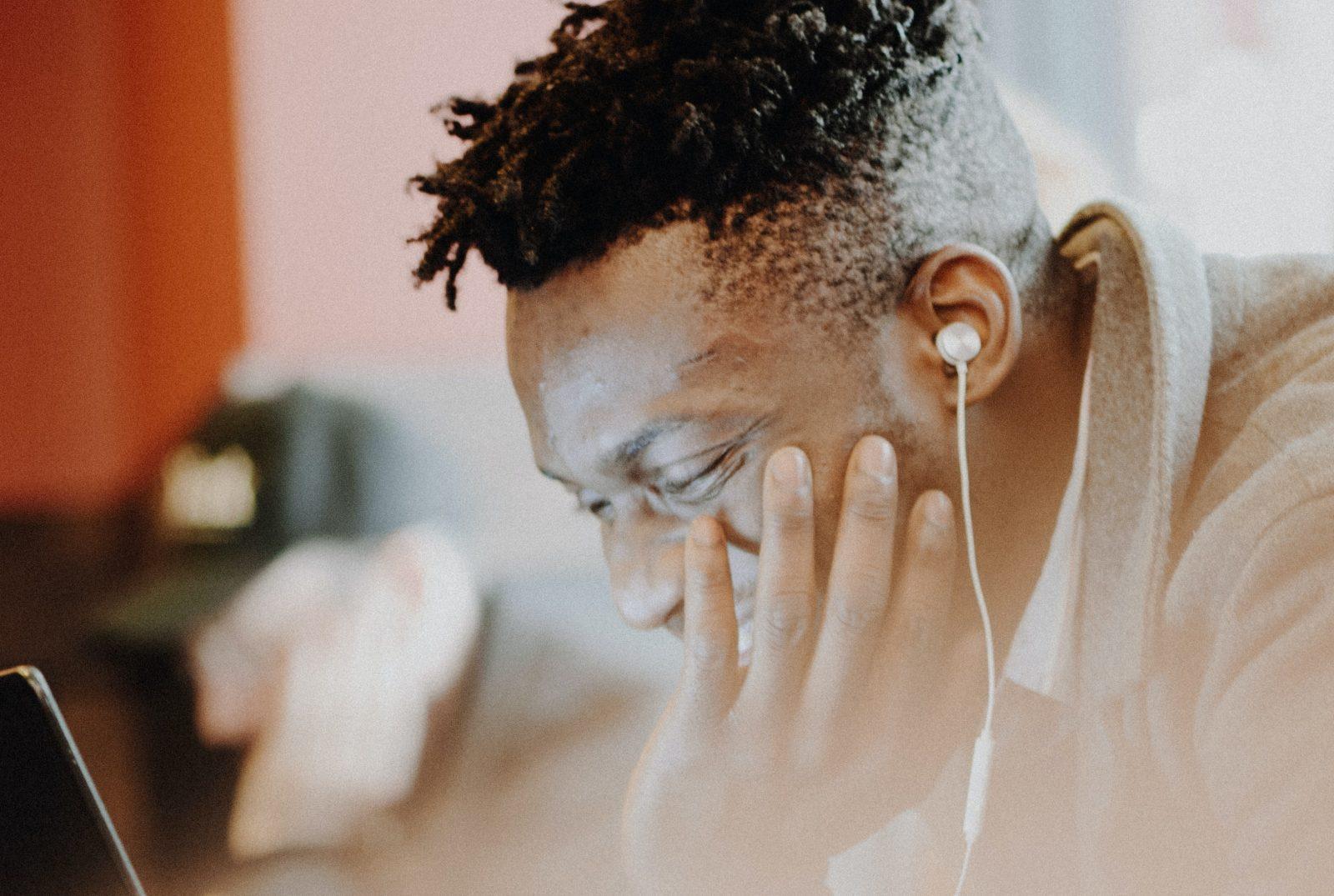 Ihminen katsoo alaspäin ja kuuntelee kuulokkeilla.